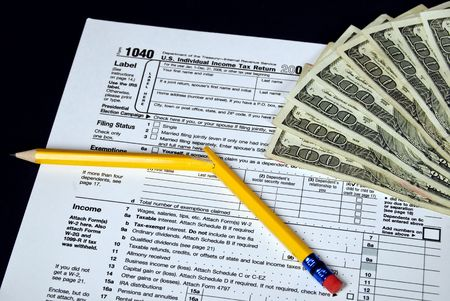 household money: Broken pencil and hundred dollar bills on an income tax form. Stock Photo
