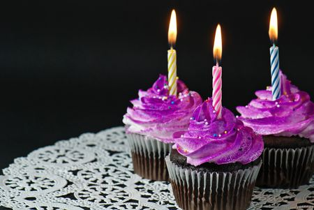 Candles in chocolate cupcakes with airbrushed frosting.