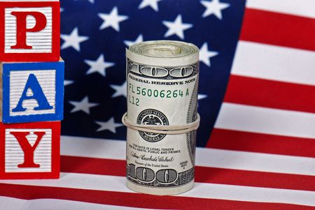 Toy blocks and roll of cash on American flag.