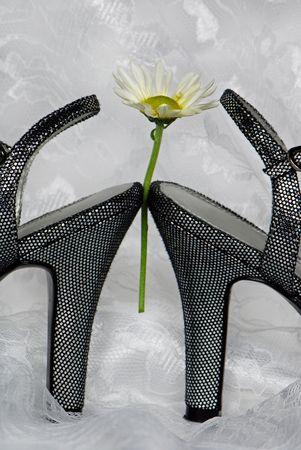 heel strap: Single daisy between a pair of silver high heels.