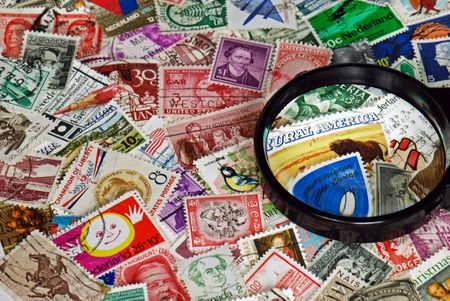 priceless: Magnifying glass on vintage stamps.
