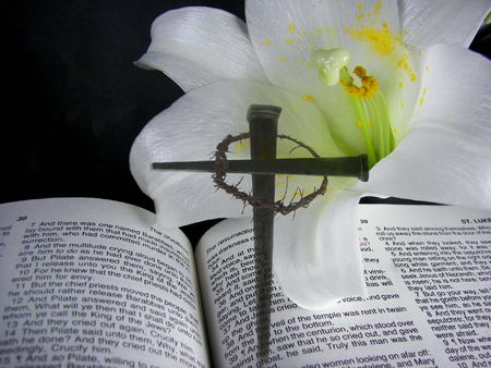 scripture: Easter lily on Bible with cross created with nails. Stock Photo