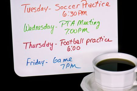 Cup of coffee with a busy week schedule on a dry erase board. Imagens