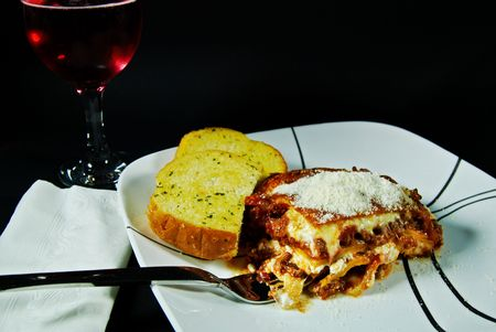 Glass of wine with a lasagna dinner. photo