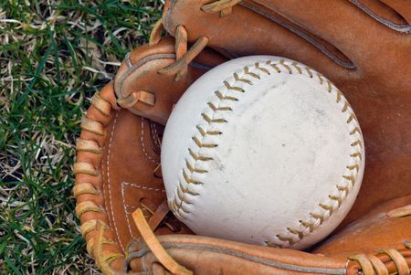 Softball in a worn glove.