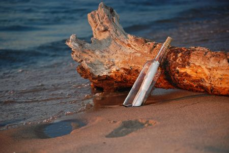 Message in a bottle leaning on driftwood. Stock Photo - 4773169