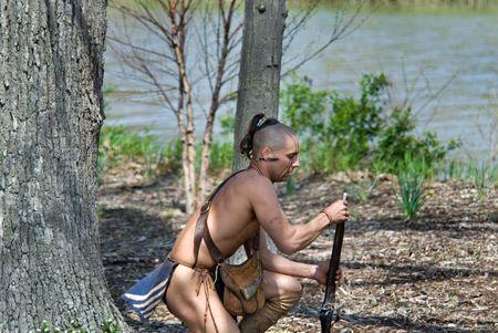 indian brave: Indian warrior loading vintage gun. Stock Photo