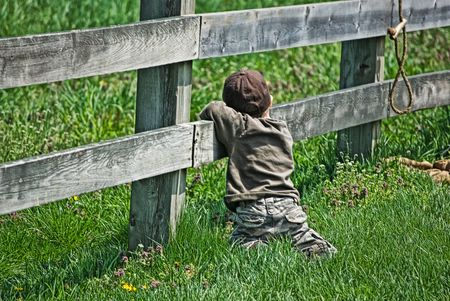 Young boy hanging on a farm fence.