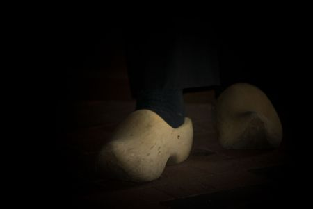 elusive: Dutch wooden shoes in the dark shadows. Stock Photo