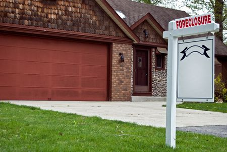 Foreclosure sign in front of a house in the suburbs. photo