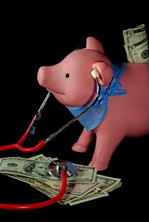 Piggy bank with stethscope on a pile of money. photo