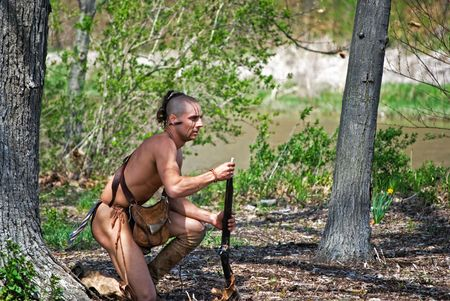 guerriero indiano: Indiano guerriero ricarico la sua pistola d'epoca.