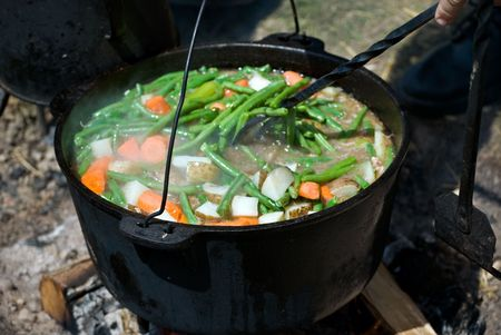 soup kettle: Vegetale stew simmering in a vintage kettle over a fire.