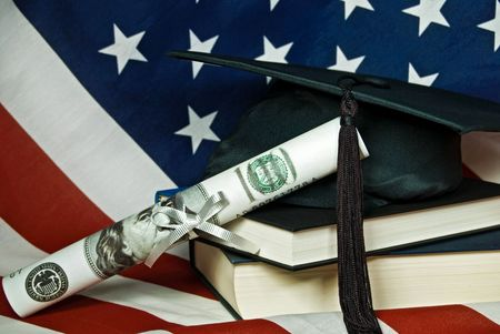 Graduation cap with cash diploma on an American flag.