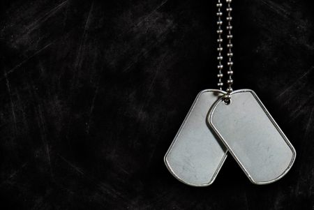 ball and chain: Dangling military dog tags on a grunge background. Stock Photo