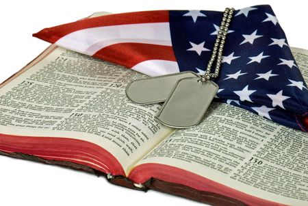 Dog tags and folded flag on Bible. Фото со стока