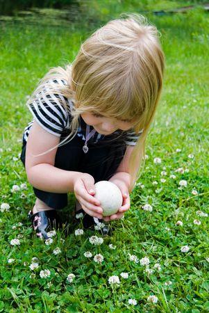 Little girl holding a goose egg. photo