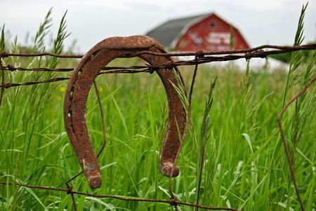 Rusty horseshoe on barb wire fence. Stock Photo