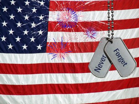 Military dog tags and fireworks on an American flag. Stock Photo