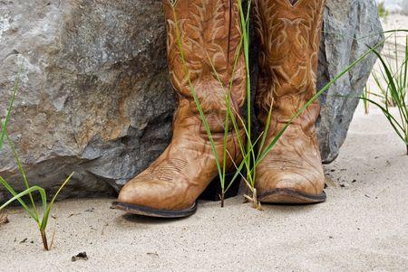 cowboy boots: Cowboy boots by granite boulder. Stock Photo