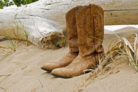 botas vaqueras: Par de botas de vaquero abandonado por un tronco flotante. Foto de archivo