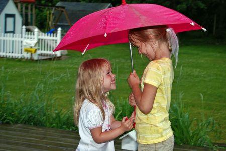 Little girls under a red umbrella in the rain. photo