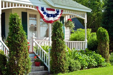 country house: Holiday flag bunting hanging from a porch. Stock Photo