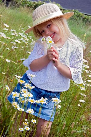 innocence: Shy little blond girl with daisy bouquet.