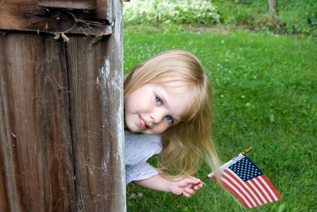 Sweet blond girl with a small American flag. photo