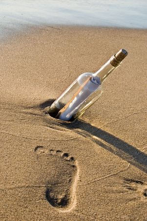 intrigue: Message in bottle on the beach with footprint. Stock Photo