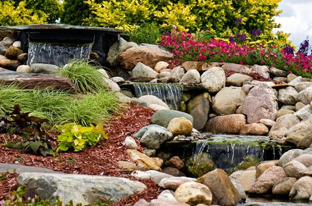 A waterfall flowing in a rock garden. Stock Photo