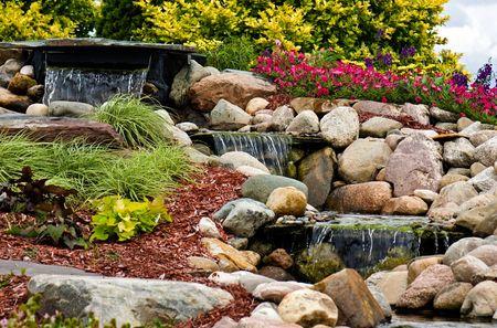 paisajismo: Una cascada que fluye en un jard�n de rocas. Foto de archivo