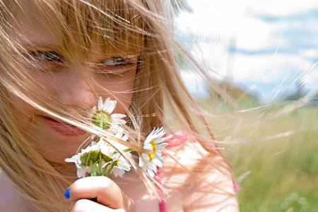 Young girl with daisy bouquet in the wind. photo