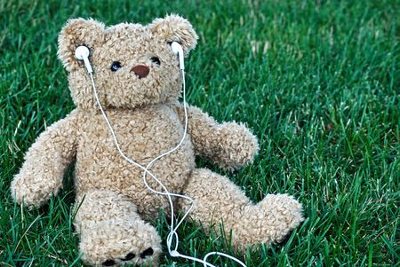 Teddy bear listening to music on a podcast. photo