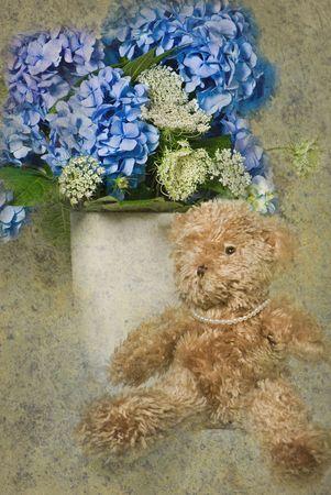 Teddy bear with hydrangea bouquet.