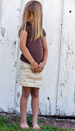 downcast: Lonely child standing by old barn. Stock Photo