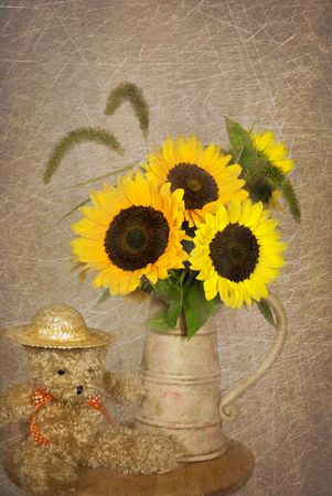 antique vase: Teddy bear with a sunflower bouquet.