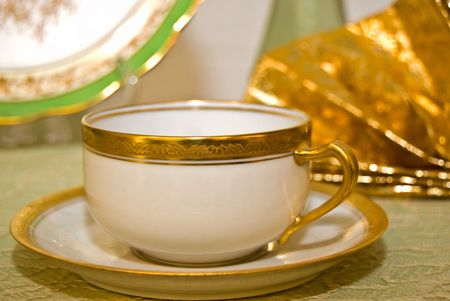 Elegant gold cofefe cup and saucer on lacy tablecloth. photo