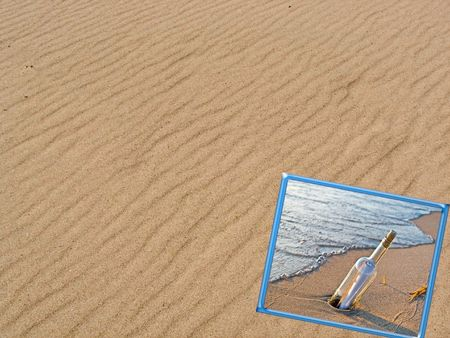 Message in a bottle in a frame on windswept beach. photo