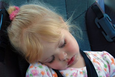 sleep: Little blond girl napping in a carseat.
