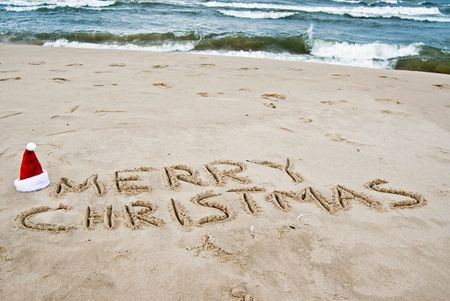 'yule tide': Santa hat and holiday greeting in sand.
