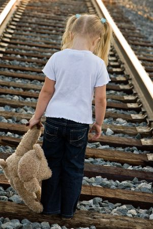 Little blond girl with teddy bear on railroad tracks.