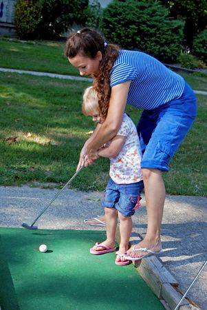 Mother teaching her daughter to golf. photo
