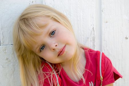 Little blond girl with a sweet expression. Imagens