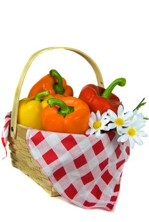 Variety of peppers in a basket with daisies. photo