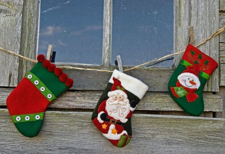 Christmas stockings hanging outside an old window. Фото со стока