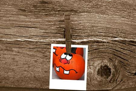 Funny pumpkin face hanging on baling twine.