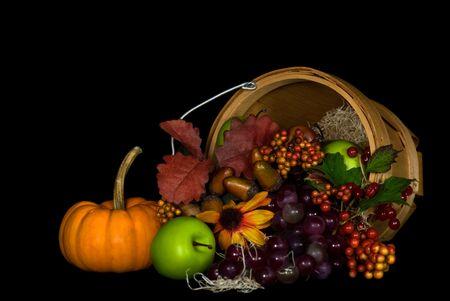 thankfulness: Overflowing wooden basket of autumn fruits.