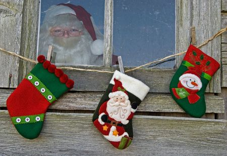 Santa in an old window with holiday stockings. photo