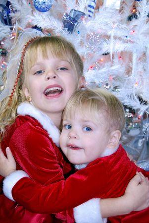 velvet dress: Little girls hugging each other by Christmas tree. Stock Photo